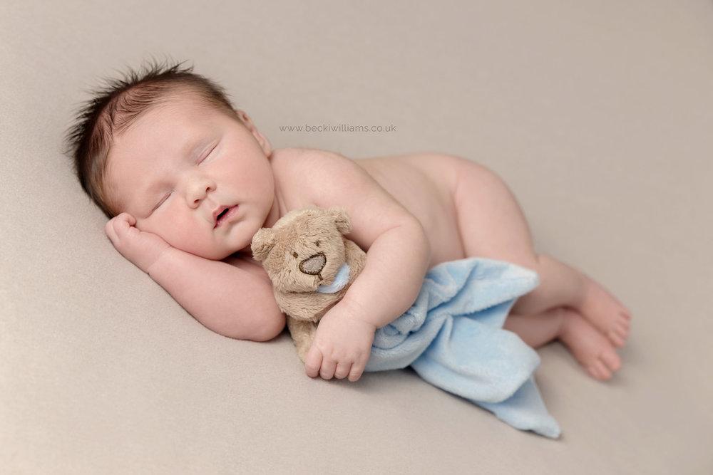 newborn baby boy naked, cuddling a teddy at his photo shoot in hemel hempstead