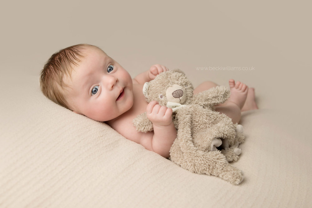 7 week old baby girl lays awake on a cream blanket staring into the camera. she is hugging her brown toy bear comforter and looks happy.