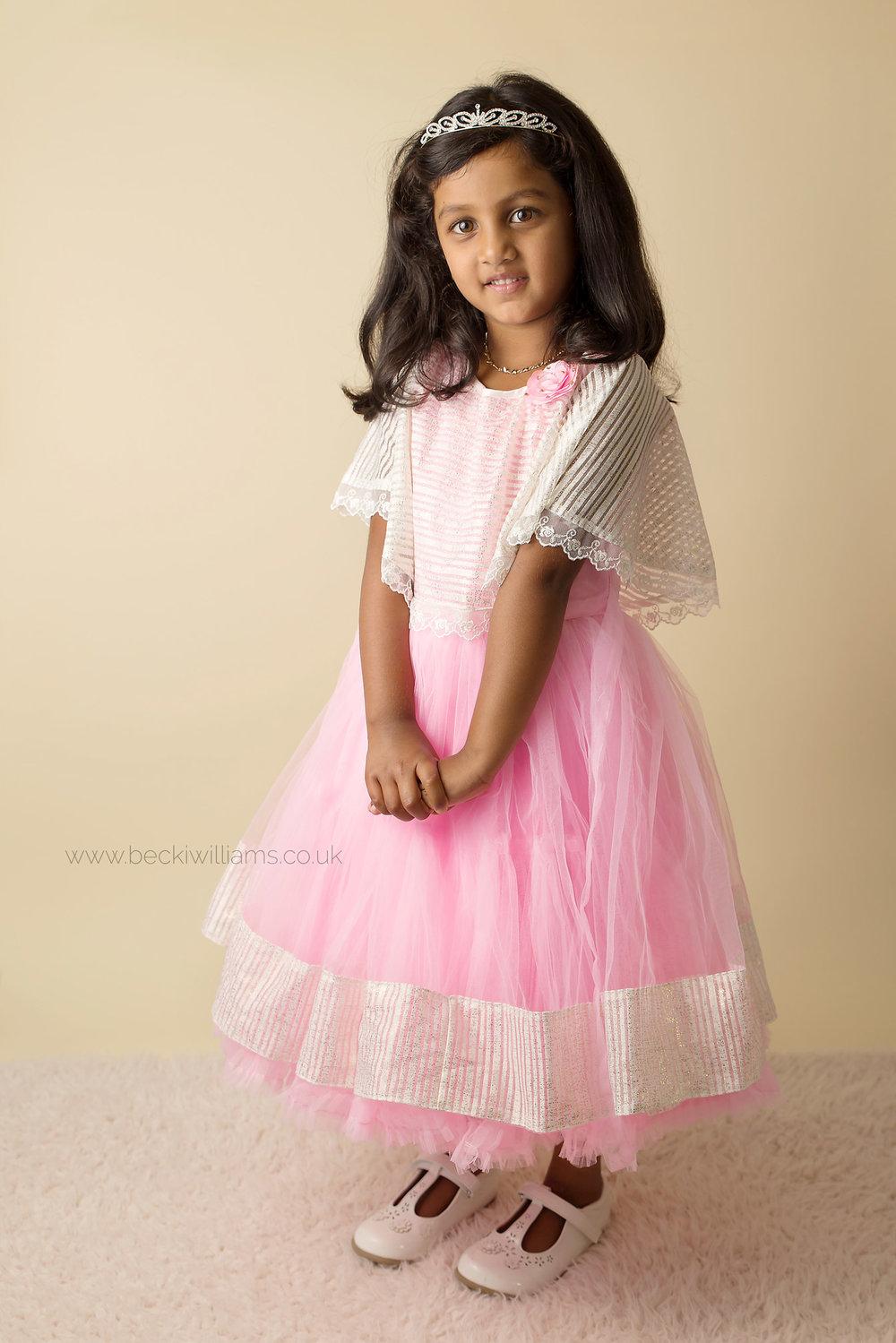 5 year old standing in a pink dress in a studio setting in hemel hempstead