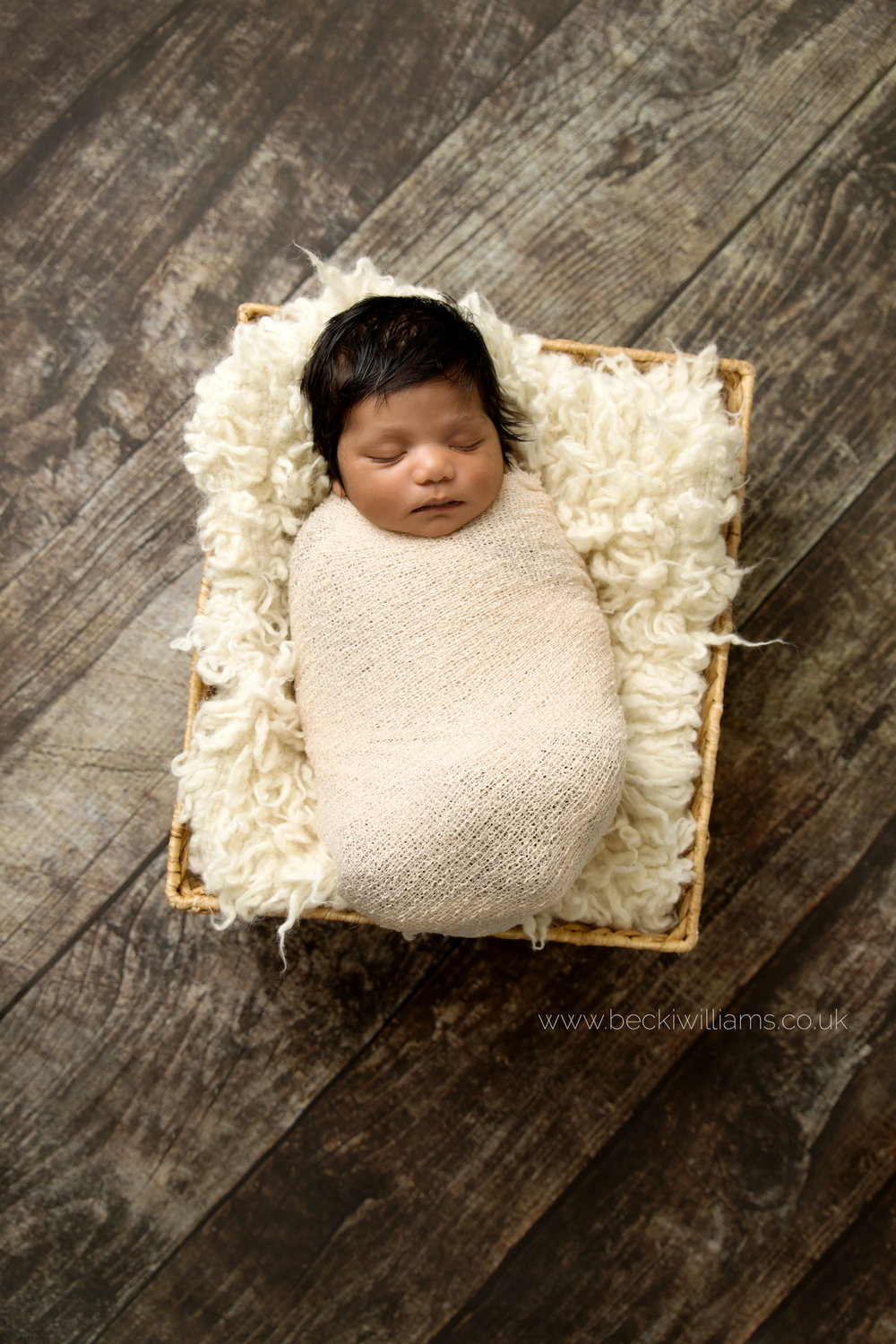 newborn baby girl wrapped in a cream wrap in a basket on a wooden floor