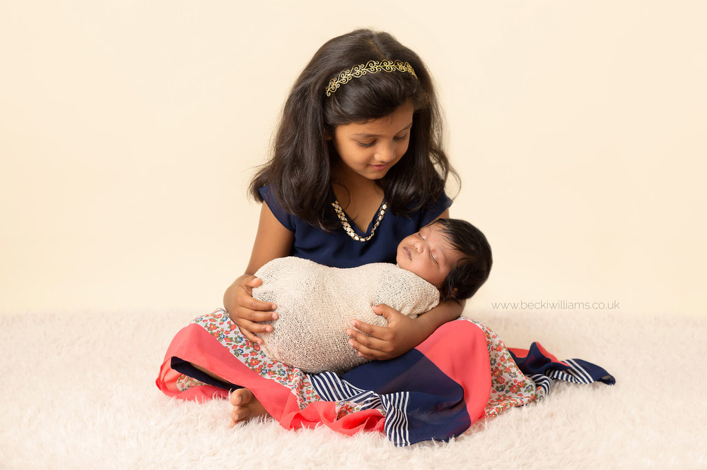 newborn baby in her sisters arms for her newborn photo shoot in hemel hempstead