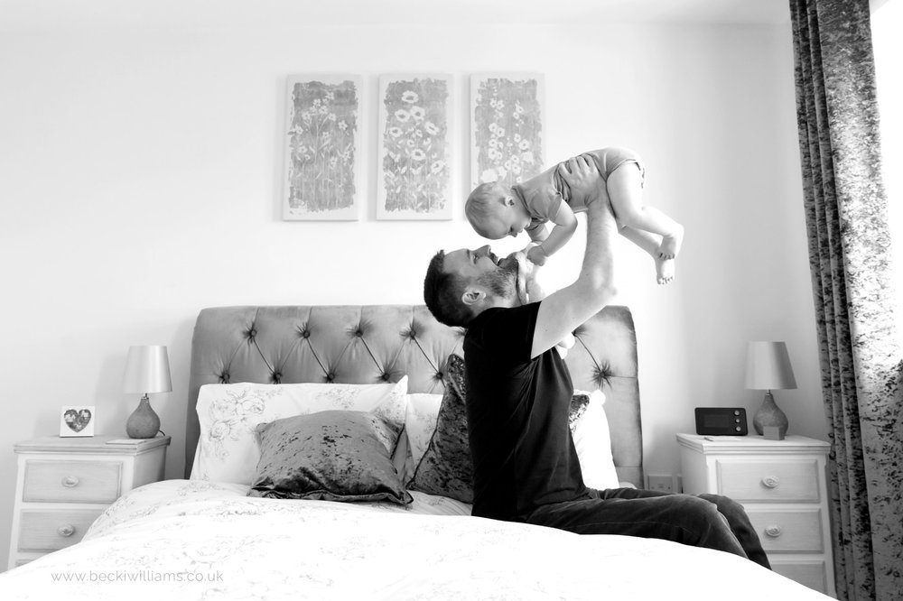 dad lifts his baby daughter into the air while sitting on a double bed