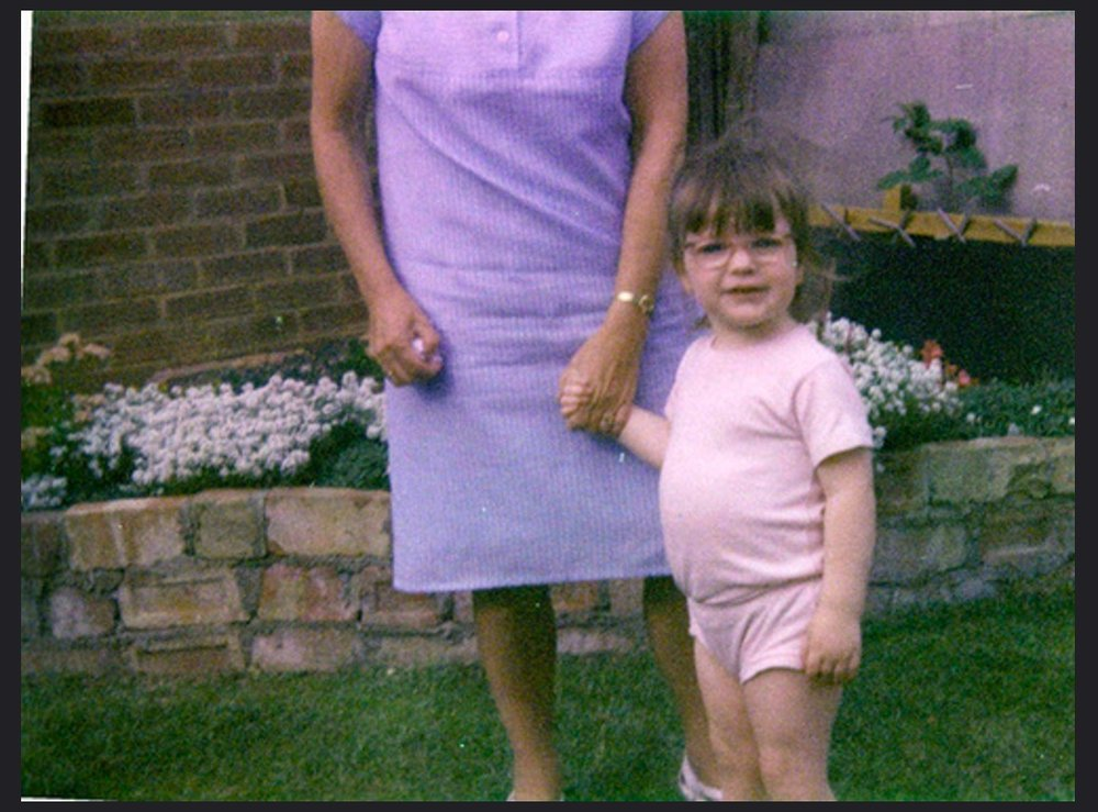 young toddler in the 80s, standing with her nan in the garden