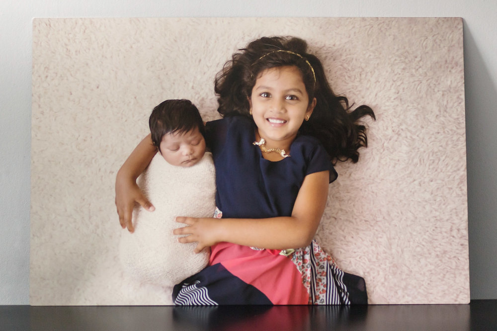 large metal wall hanging of a 5 year old laying with her new baby sister