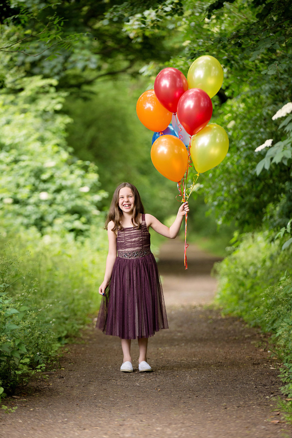 photo by becki williams photography of 8 year old girl holding balloons, laughing