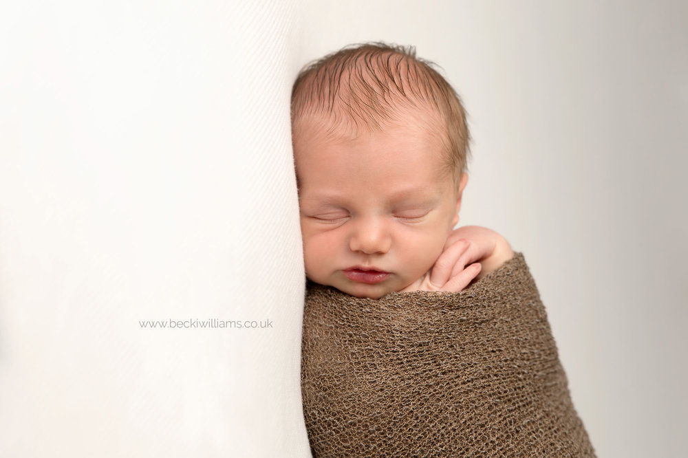 sleeping newborn baby boy wrapped in a brown wrap at his newborn baby photo shoot in hemel hempstead