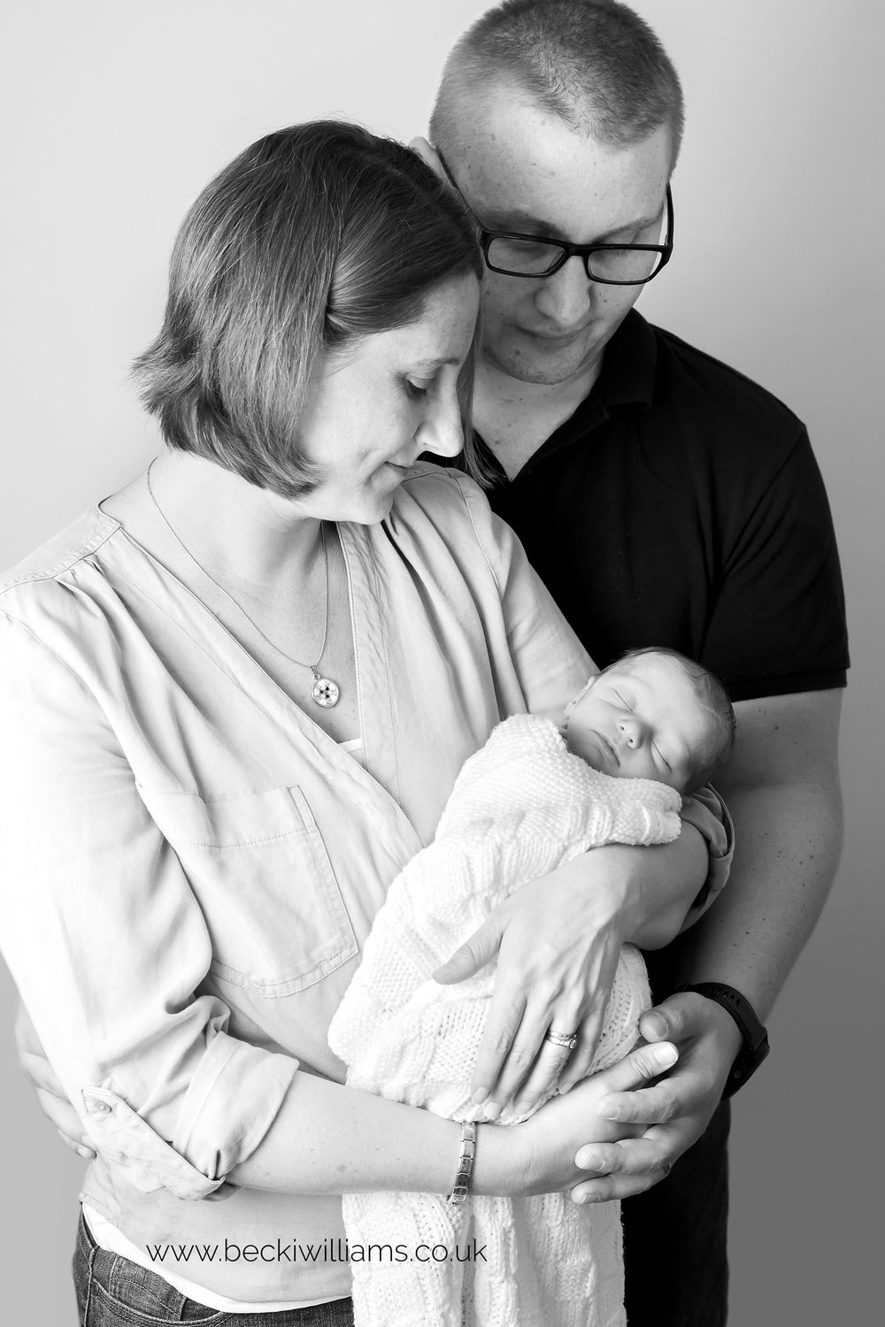 Parents Holding Their Newborn Baby In Black And White