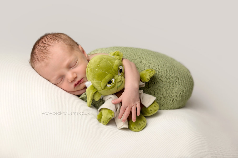 newborn baby boy wrapped in green holding a toy yoda at his newborn baby photo shoot in hemel hempstead