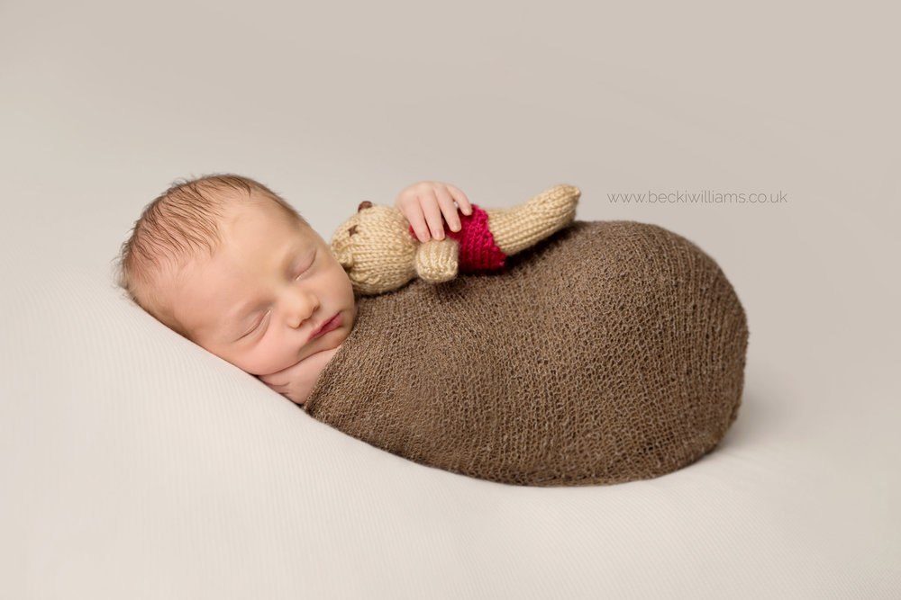 sleeping newborn baby boy wrapped in a brown wrap and holding a teddy at his newborn baby photo shoot in hemel hempstead