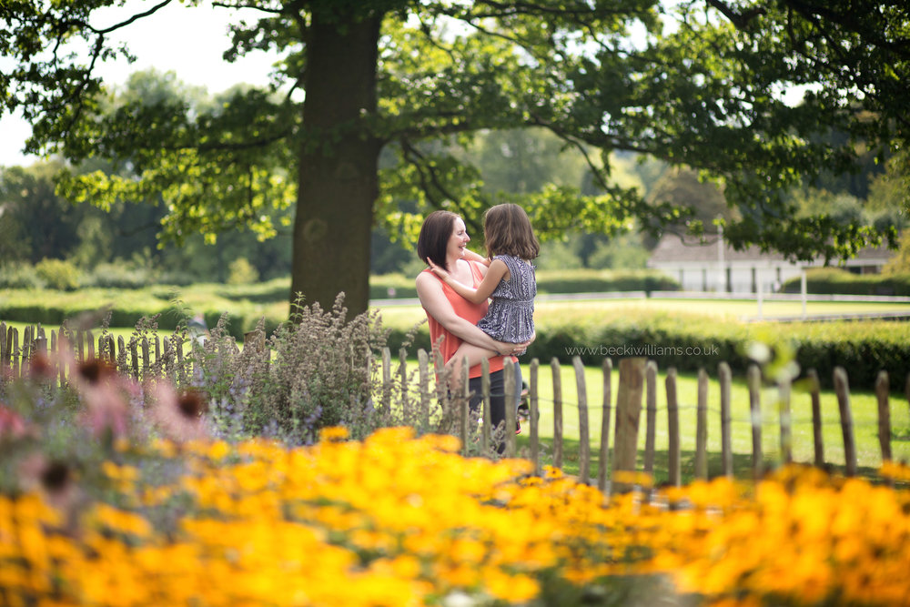 mum and daughter stand by flower bed in gadebridge park, hemel hempstead