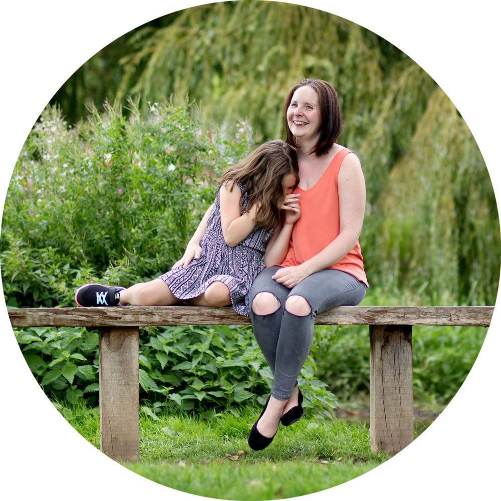 mum and daughter sit laughing on a park bench in hemel hempstead