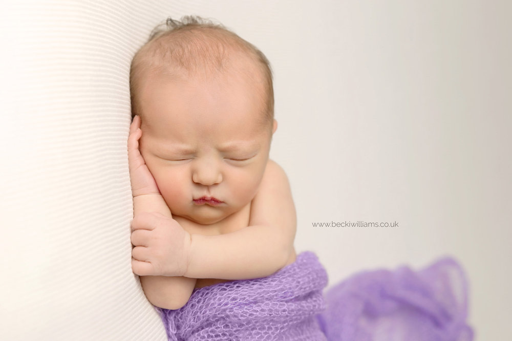 sleeping newborn baby covered in a purple blanket at her professional newborn photo shoot in hemel hempstead