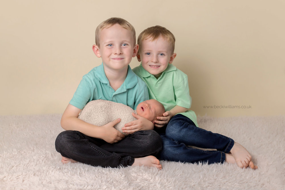two proud big brothers sit holding their newborn baby sister