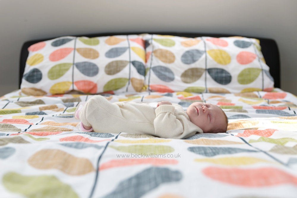 newborn baby girl laying sleeping on a large bed
