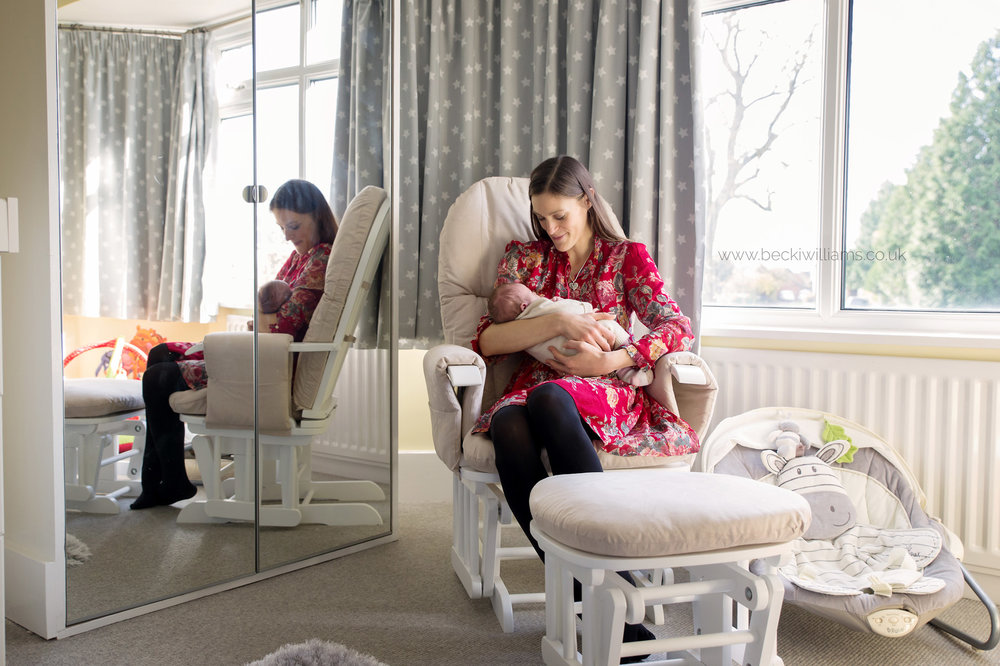 new mum sitting her newborn baby girl's neutral nursery on a rocking chair, holding her baby
