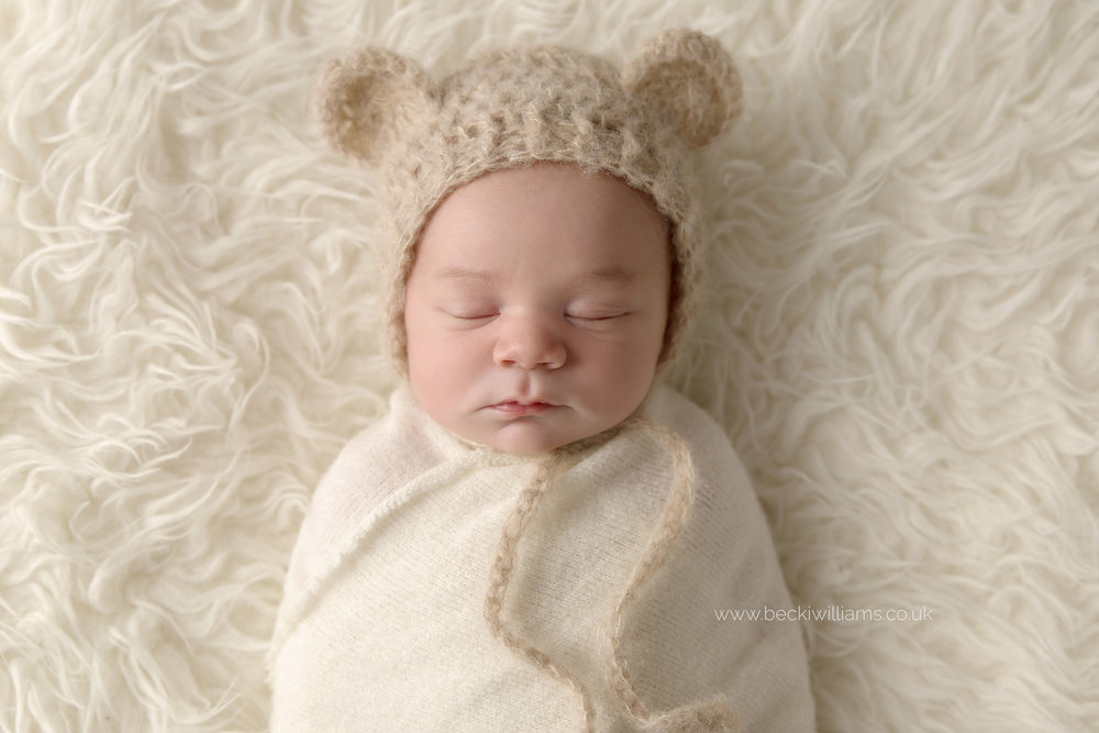 newborn baby boy sleeping on a white fluffy blanket, wrapped in a white blanket and wearing a brown hat with bear ears