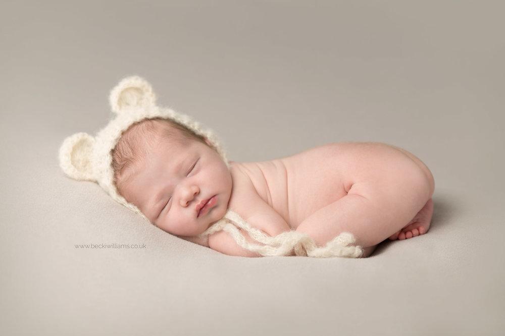newborn baby lays sleeping on a grey blanket wearing a bonnet with bear ears
