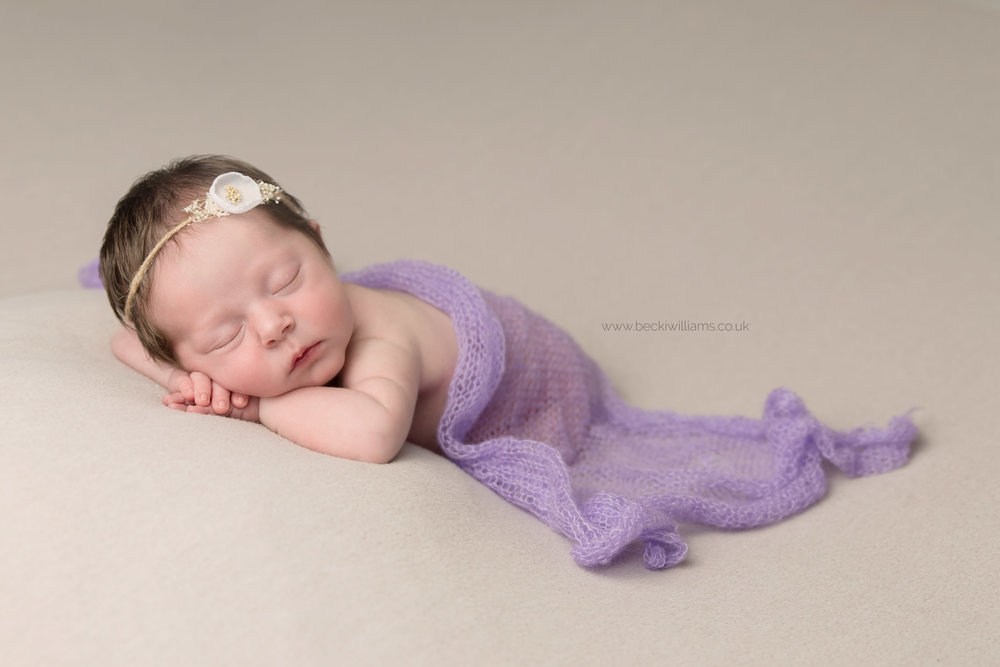 newborn girl laying on her front covered in a pruple blanket and wearing a white flower headband for her newborn photo shoot in hemel hempstead