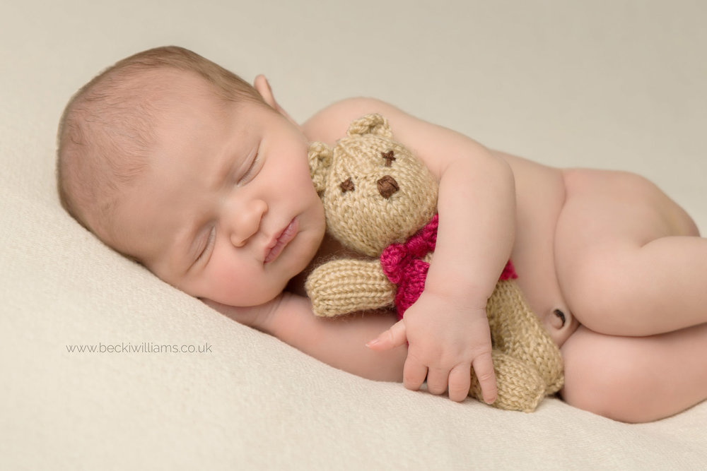 newborn photo shoot of baby girl laying on her side holding a small teddy bear in a red waist coat