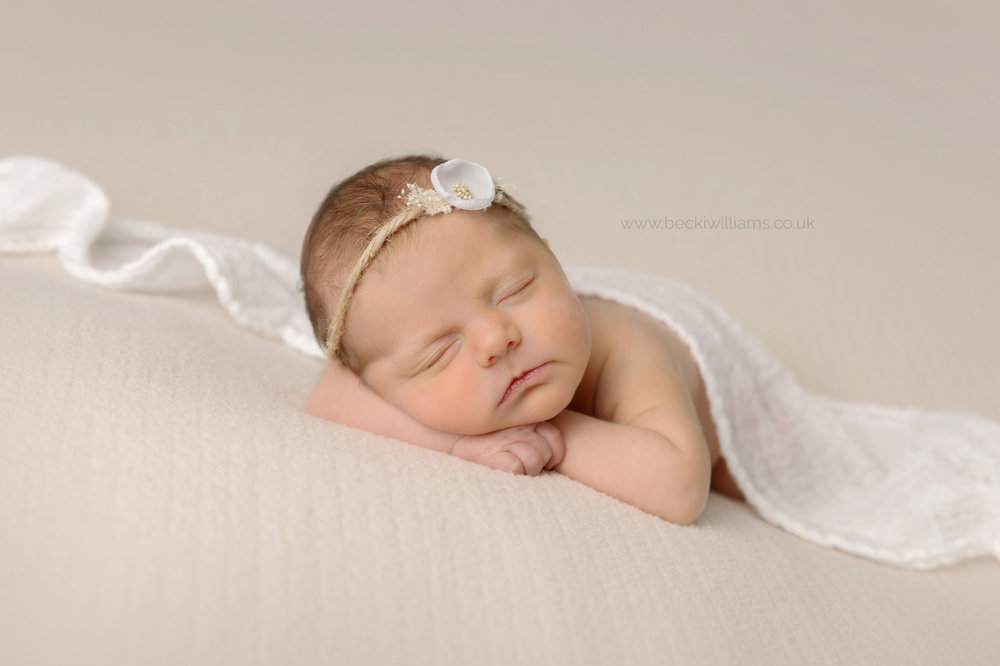 Newborn girl laying with her head on her hands covered in a white blanket and wearing a white flower headband