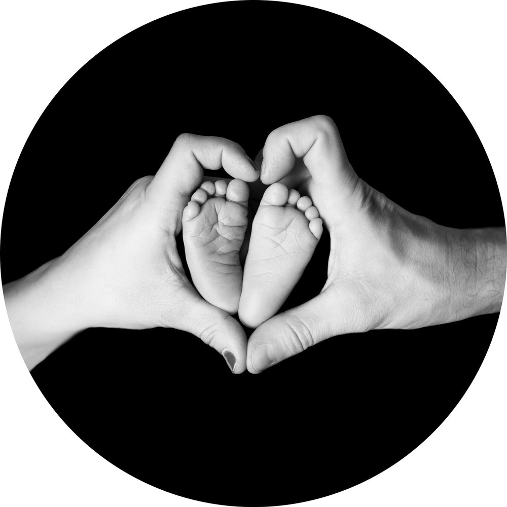 black and white images of a newborn babies feet in his parents hands while they make a heart shape