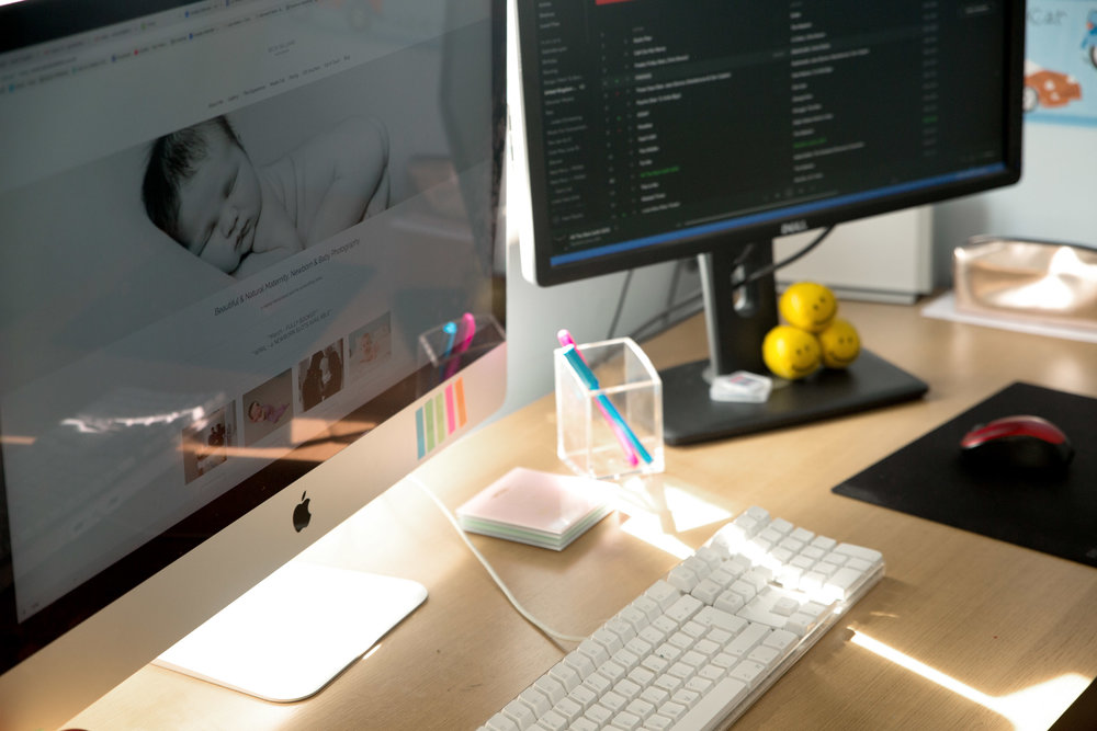 sun shines on a desk with becki williams photography website on one screen and spotify on the other