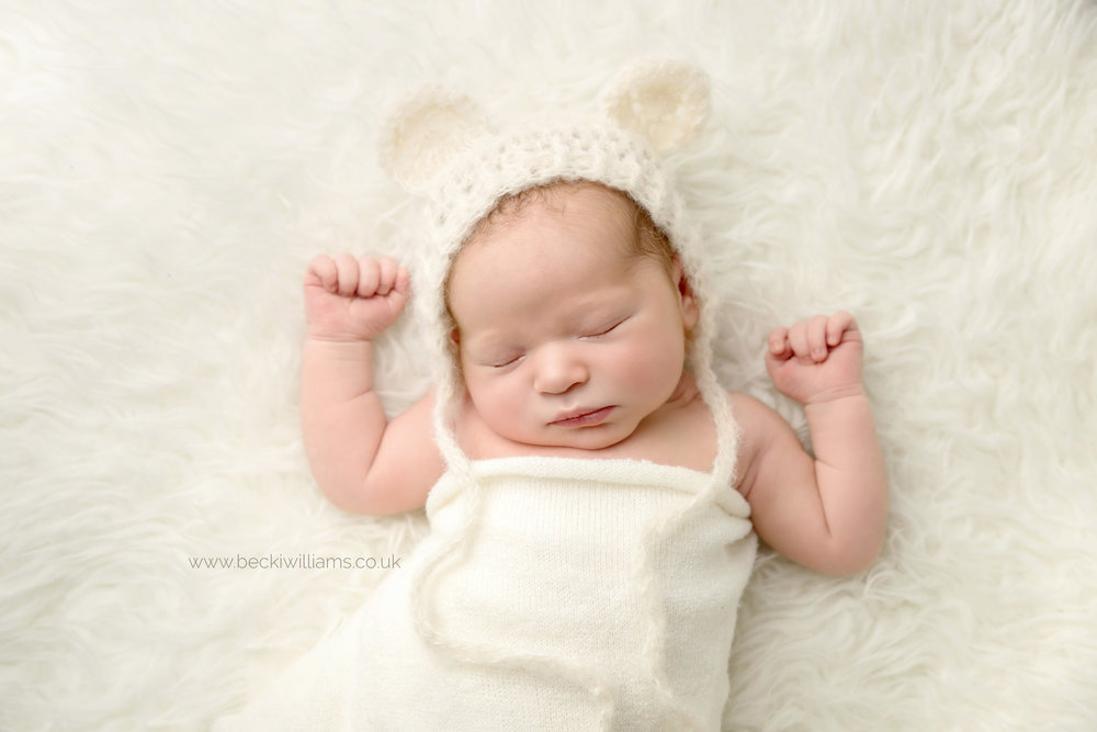 photo of a newborn baby boy laying on a white fluffy blanket, wearing a bonnet with bear ears and wrapped in a cream blanket.