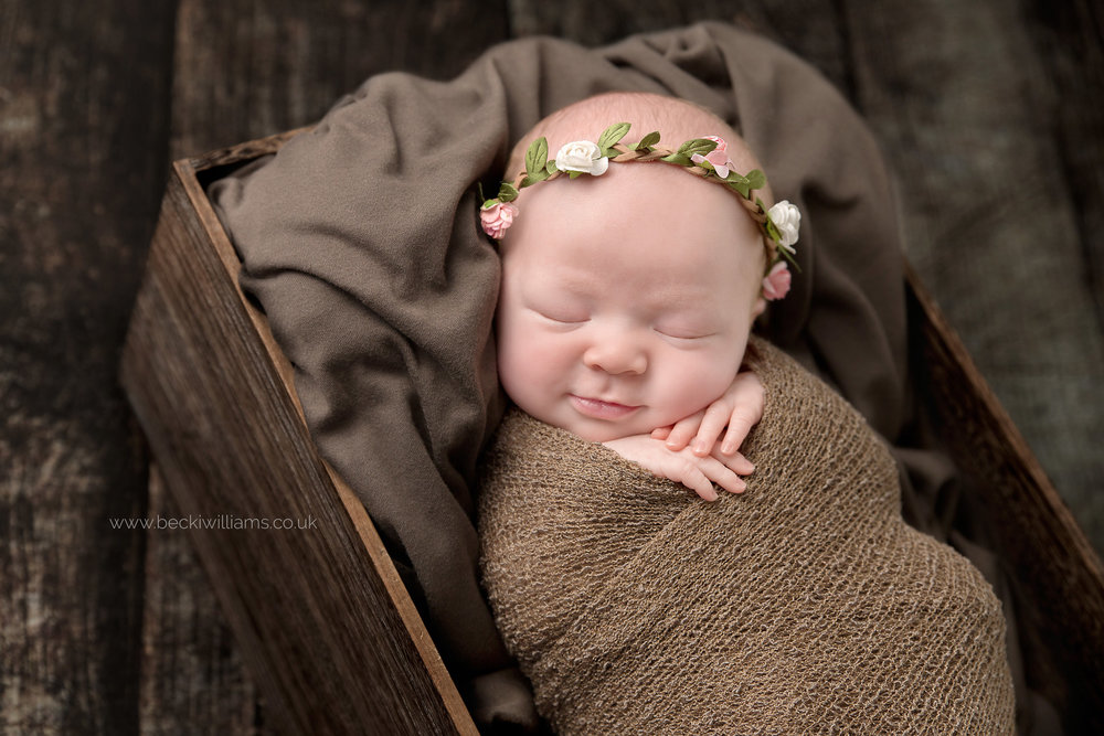 newborn girl smiling slightly while wrapped in a brown blanket and laying in a crate on a wooden floor for her posed newborn photo shoot in hemel hempstead