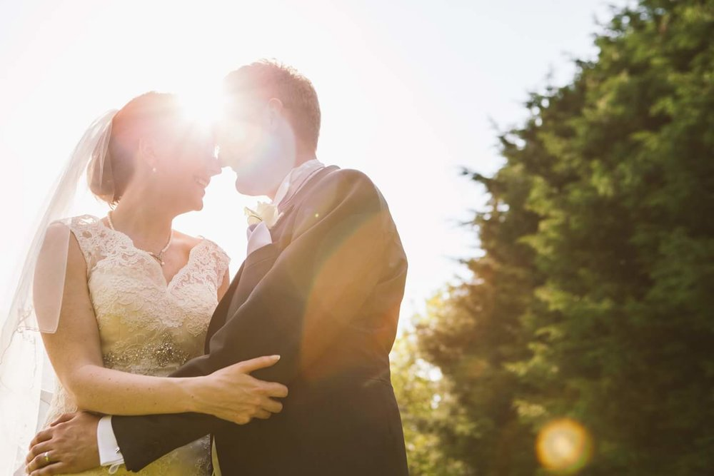 a couple standing on their wedding day with a sun flare coming from behind their head