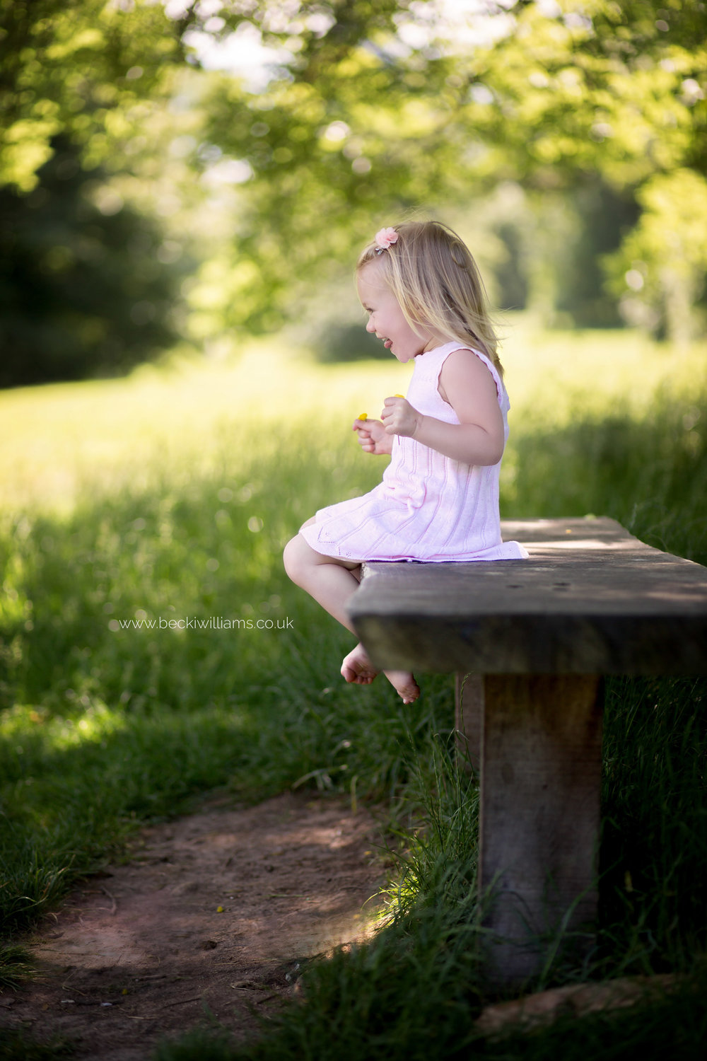 little girl sitting, smiling on a bench in gadebridge park, hemel hempstead