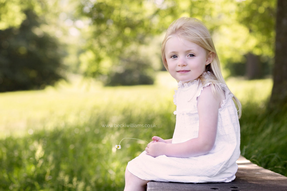 little girl sitting on a bench, holding a flower in gadebridge park, hemel hempstead