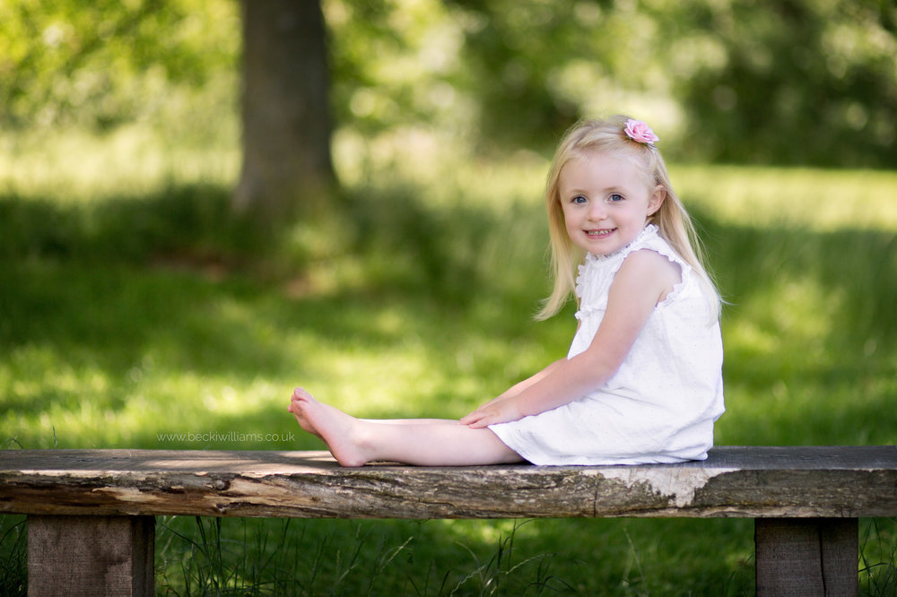 little girl sitting on a bench in gadebridge park, hemel hempstead