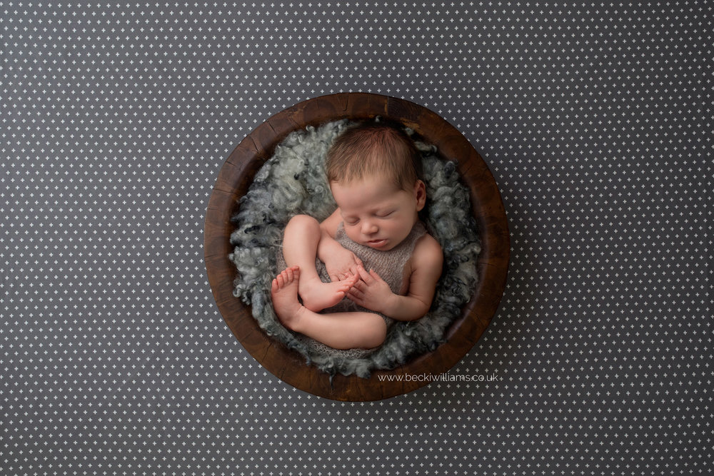 newborn boy lays asleep on grey fur, inside a wooden bowl, which is sitting on a spotty background for his newborn photo shoot in hemel hempstead
