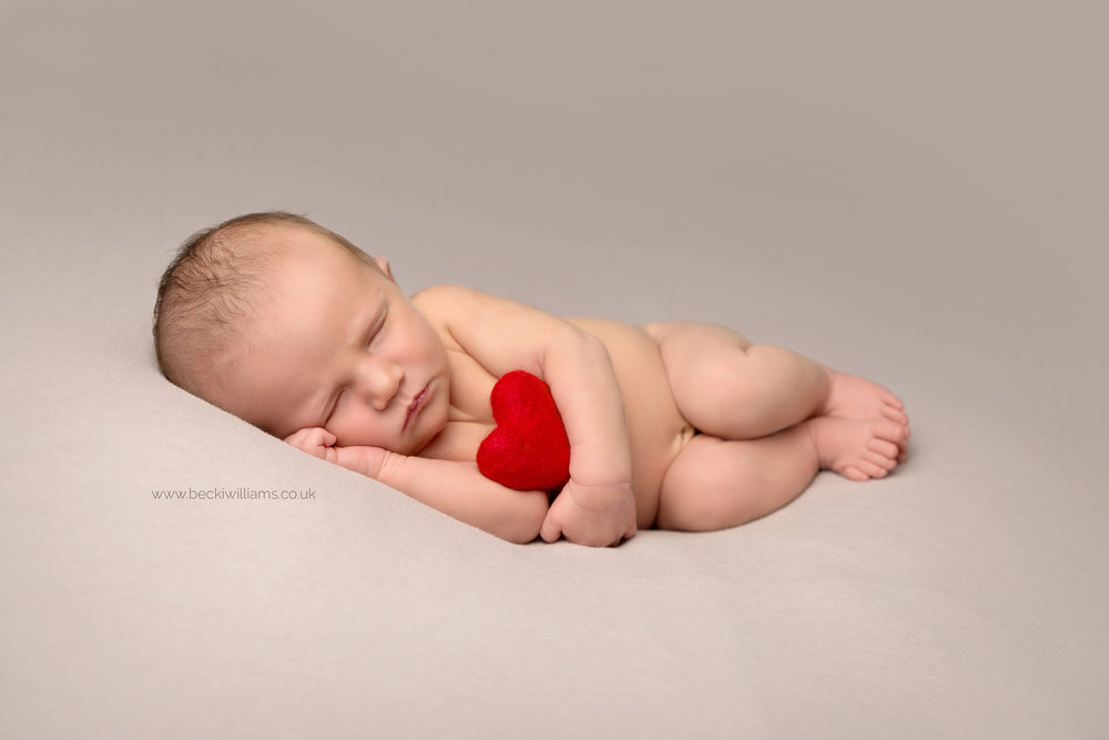 cute newborn baby girl laying on her side holding a red heart at her newborn photo shoot in Hemel hempstead