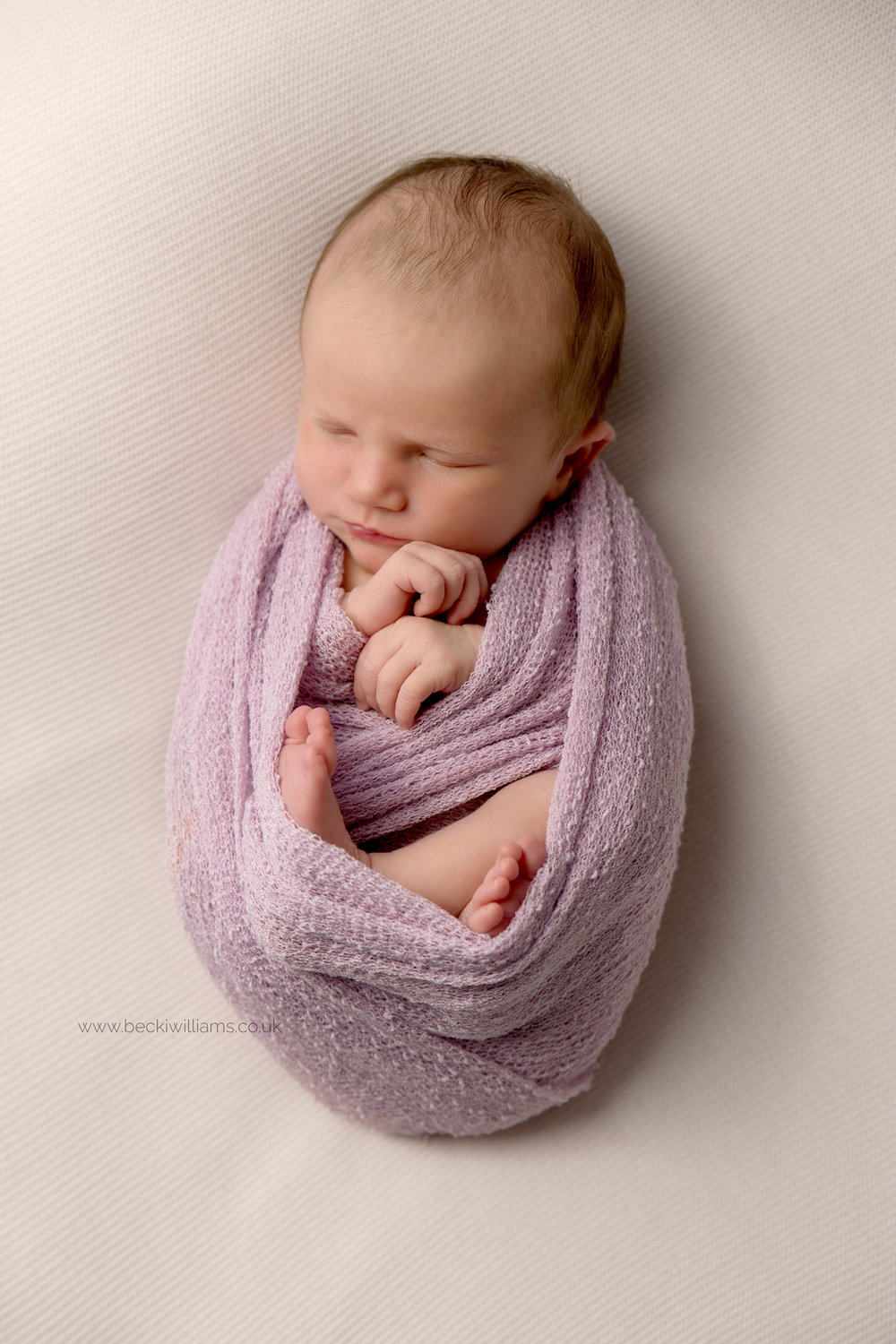 newborn baby girl wrapped in a pink wrap for her newborn photo shoot in Hemel hempstead