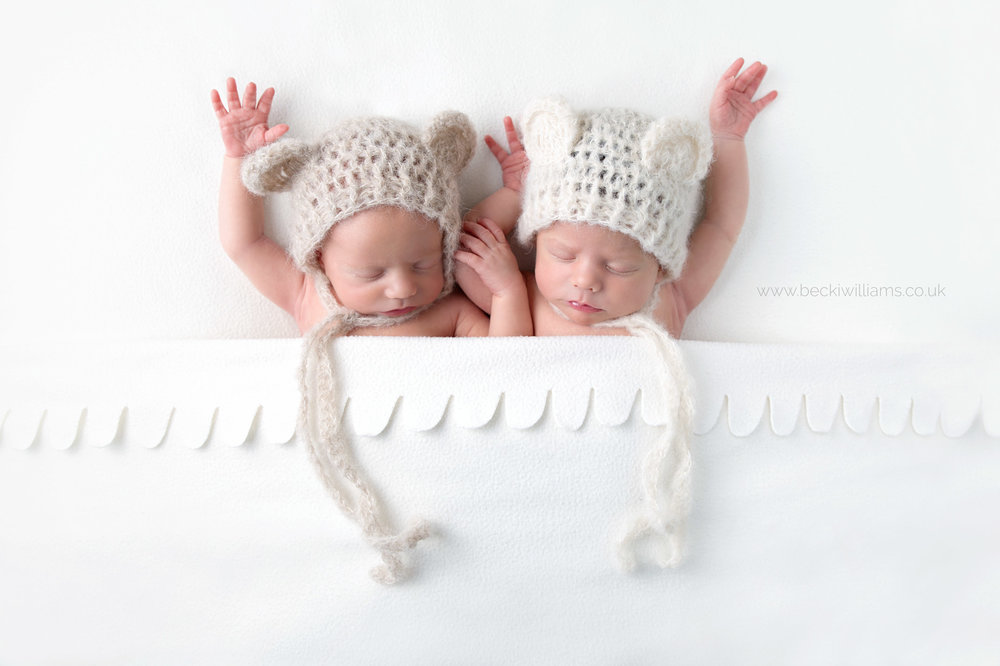 newborn twins wearing bear hats under w white blanket with their arms above their heads at their newborn photo shoot in Hemel hempstead
