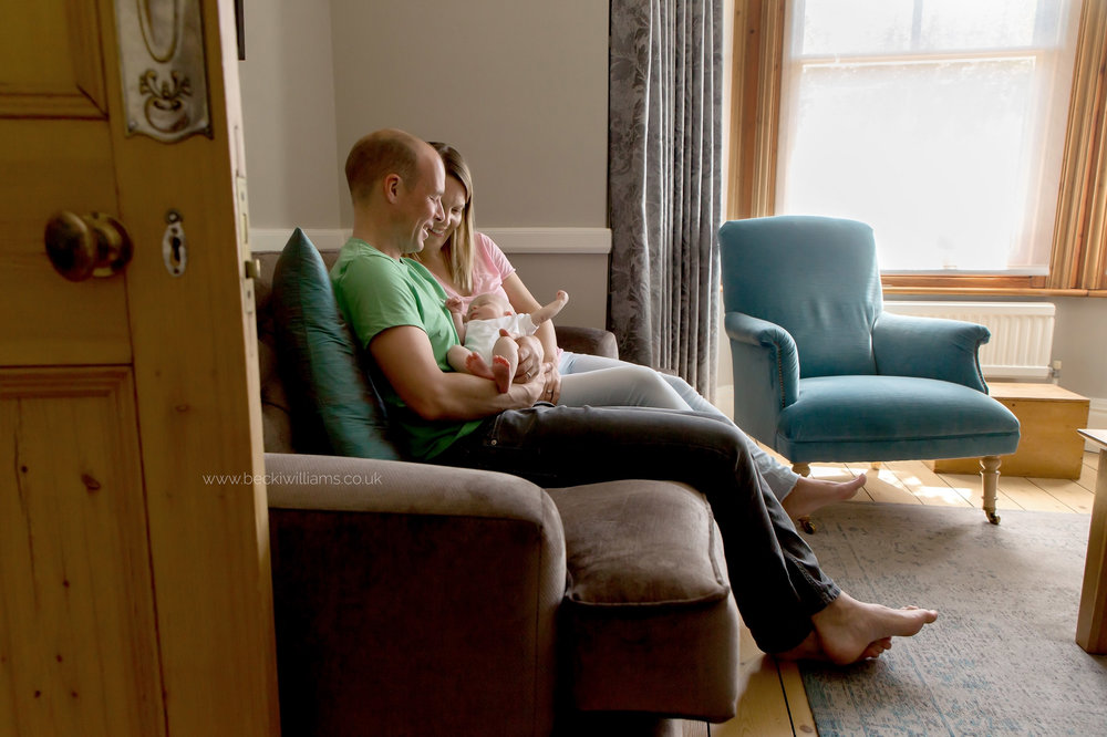 family sitting on their sofa with their newborn baby for their photo shoot in st albans