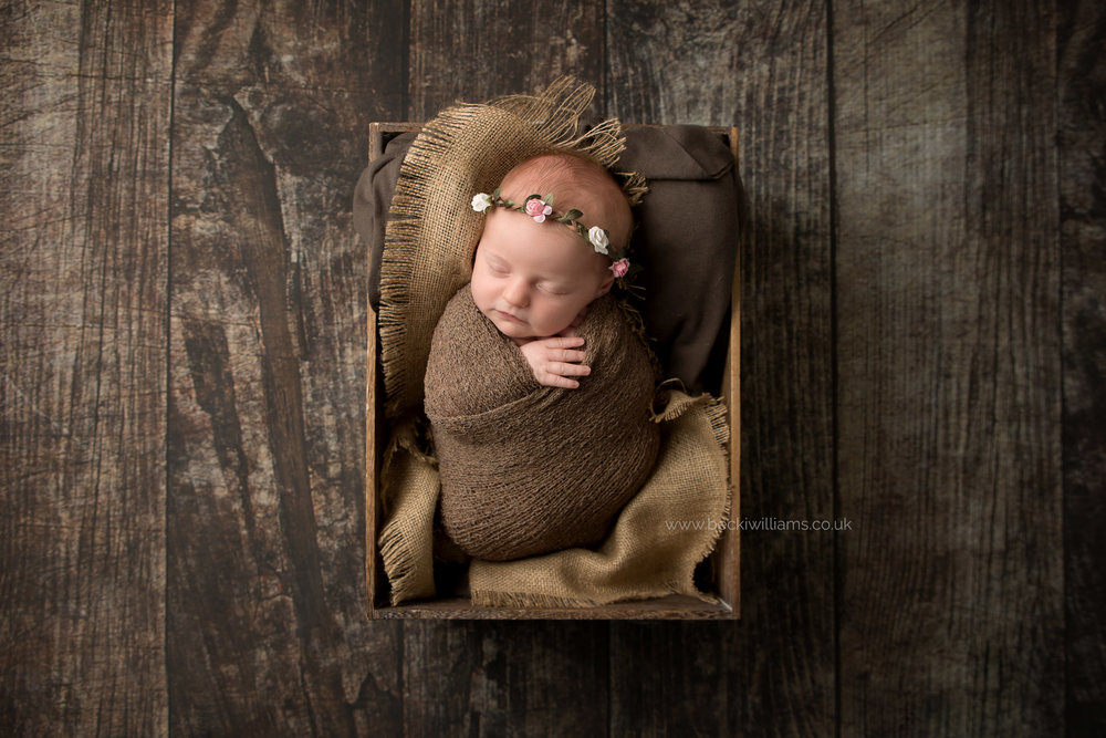 newborn baby girl wrapped up in a brown blanket in a brown crate on a wooden floor at her newborn photo shoot in hemel hempstead