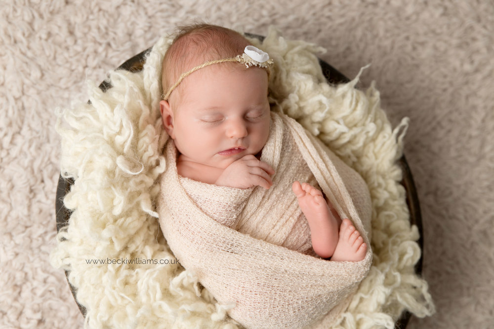 newborn baby gily wrapped in a cream blanket on cream fuff in a brown bowl for her newborn photo shoot in hemel hempstead
