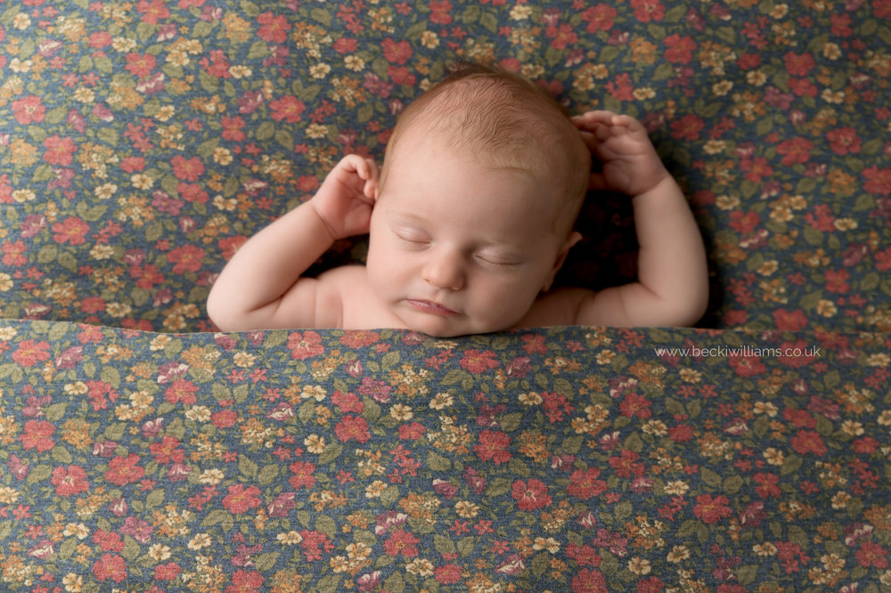 newborn girl, asleep, laying on a flowery blanket for her newborn photo shoot in hemel hempstead