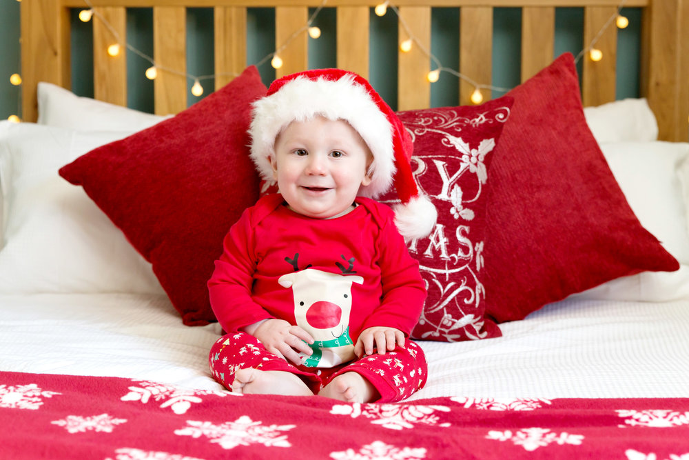 baby boy sitting on a christmassy decorated bed for a christmas photo shoot in hemel hempstead, herfordshire