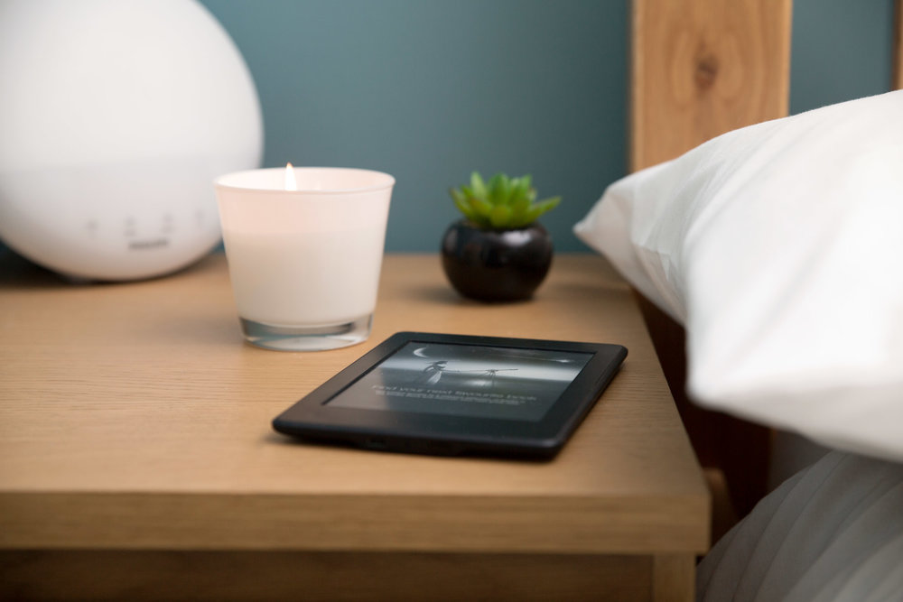 photograph of kindle on bed side table with a lit candle and succulent