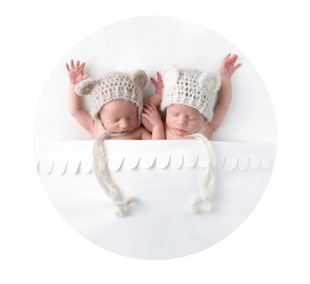 newborn twins, wearing bear hats under a white blanket for thier photo shoot in hertfordshire