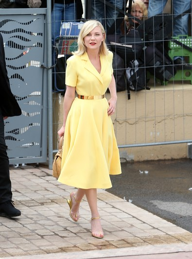 Kirsten Dunst channels Grace Kelly in a lemon-yellow Dior shirtdress and and a retro basket bag.