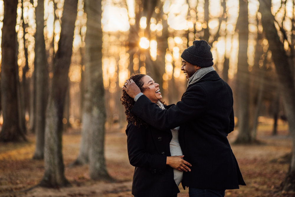 Man brushes hair out of pregnant woman's face in sunlit photo by Huntsville and Madison Alabama maternity photographer Rachel K Photo