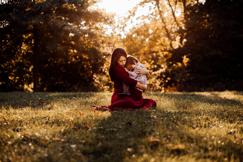 Pregnant woman in red dress snuggles sleepy toddler by Huntsville and Madison Alabama maternity photographer Rachel K Photo