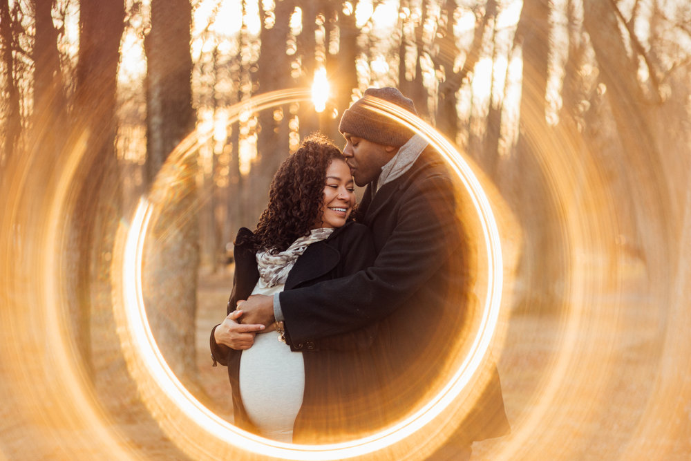 Man kisses pregnant wife in ring of fire maternity photo by Huntsville and Madison Alabama maternity photographer Rachel K Photo