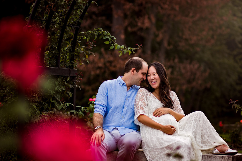 Pregnant woman laughing with man in rose garden by Huntsville and Madison Alabama maternity photographer Rachel K Photo