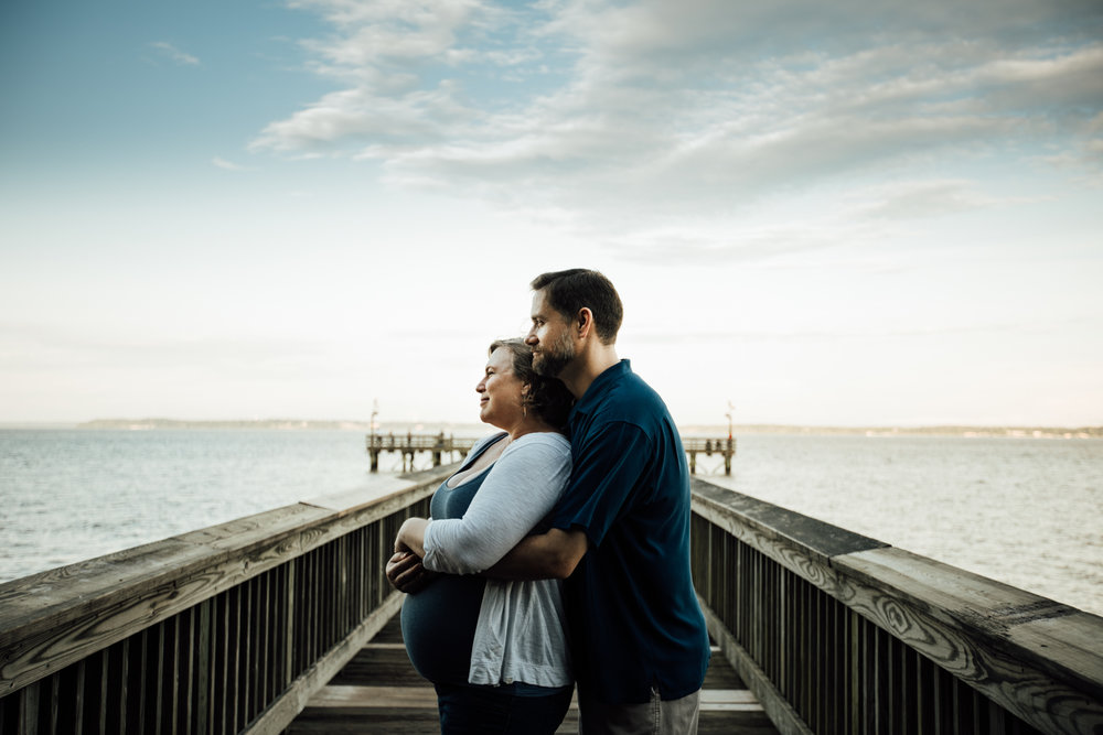 Pregnant woman being hugged by man on pier by Huntsville and Madison Alabama maternity photographer Rachel K Photo
