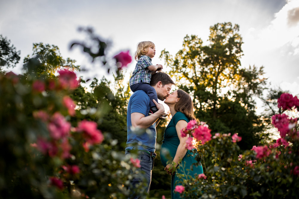 Pregnant man and woman kiss with toddler on shoulders by Huntsville and Madison Alabama maternity photographer Rachel K Photo